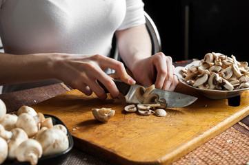 man cutting mushrooms on wooden cutting board