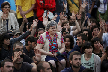 Demonstrators raise their hands during a public assembly at Madrid's landmark Puerta del Sol