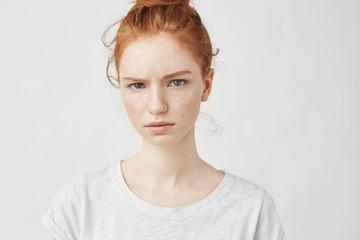 Portrait of beautiful upset redhead girl looking at camera.