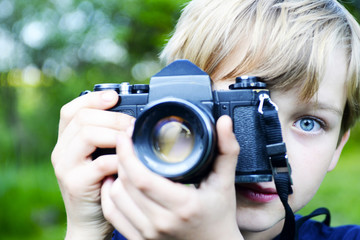 Little child blond boy with an old camera shooting outdoor. Kid taking a photo using a vintage retro film camera.