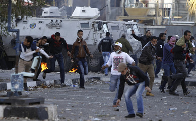 Protesters opposing Egyptian President Mursi run after riot police during clashes in Port Said City