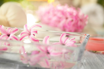 Beautiful spa composition with flowers in glass tray on table
