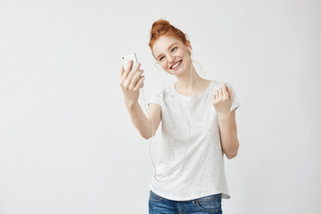 Cheerful foxy girl smiling speaking on phone in headphones.