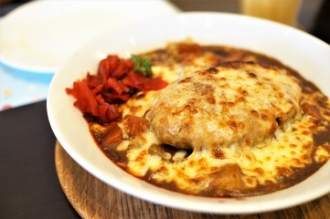 A dish of Hamburg curry rice roasted with cheese on top seen on the table