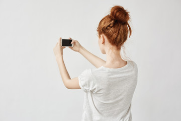Beautiful redhead girl holding phone standing back to camera.