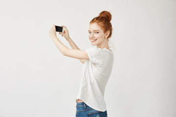 Redhead girl holding phone standing back looking to camera.