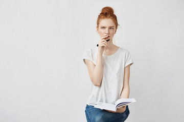 Beautiful redhead girl making notes thinking sitting over white background.