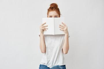 Beautiful foxy girl hiding face behind book looking at camera.