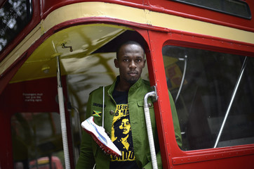 Sprinter Usain Bolt of Jamaica poses during a photoshoot  beside a traditional routemaster bus in London