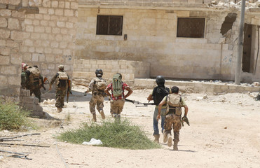 Free Syrian Army fighters hold their weapons as they run in the southern part of Maarat Al-Nouman, Idlib