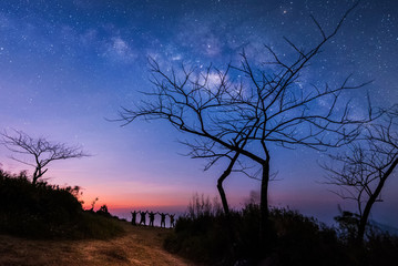 Milky Way.Night sky with stars and silhouette of standing happy peoples raised up arms. Blue milky way with people on the mountain.Background with universe. Night landscape. Travel freedom concept.