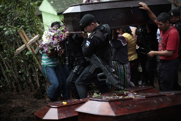 Police officers help to carry coffin of Gonzalez family member shot dead during attack by unknown assailants during funeral at Las Escobas village in Villacanales