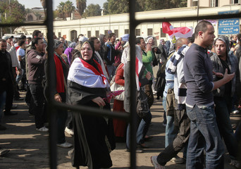 Demonstrators, seen from a police booth, chant anti-military council slogans on their way to Tahrir square as they take part in a protest marking the first anniversary of Egypt's uprising