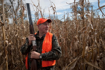 U.S. Republican presidential candidate Huckabee walks through a field of corn while participating in the Col. Bud Day Pheasant Hunt outside of Akron