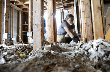 Walters works to pull baseboards and sheetrock from the studs in her basement after heavy rains caused flooding to reach her home in Boulder, Colorado