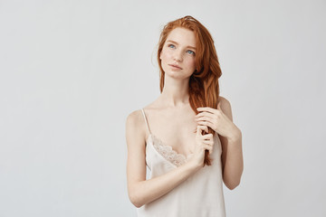 Beautiful ginger girl in sleepwear dreaming looking to distance.