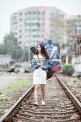 Guitar girl walking on railway tracks.