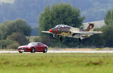 A fighter Aero L-29 Delfin losses a speed race against a Mercedes-Benz SLS sports car during the Slovak International Air Fest at the airport in Sliac