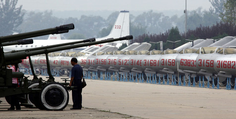 A visitor to the China Aviation Museum in Beijing, looks at old anti-aircraft guns on display next to a row of old People's Liberation Army Air Force MiG-15 fighter jets