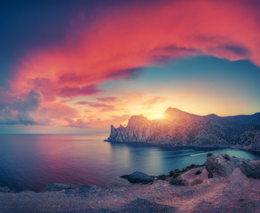 Wall Mural - Amazing mountain landscape at sunset with vintage toning. Beautiful view from the hill on the blue sea, rocks and colorful sky with red clouds and yellow sunlight. Summer seascape. Nature background