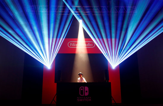 A DJ performs in front of Nintendo's logo at the presentation ceremony of its new game console Switch in Tokyo