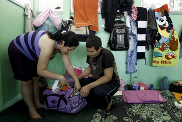 Cuban migrants Yordanys Casanoca and his wife Lislenia Fernandez prepare their luggage before their journey to the Guatemala-Mexico border at a shelter in La Cruz