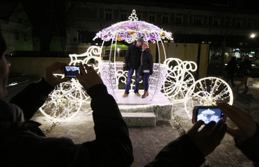 People take pictures of a couple posing with a light decoration during the annual illumination of Christmas lights at Krakowskie Przedmiescie street in Warsaw