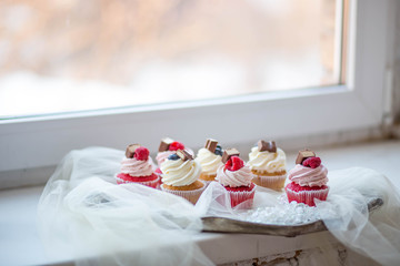 delicious cupcakes red velvet raspberry chocolate cream blueberry cream on a tray with veil close-up food sweets cakes