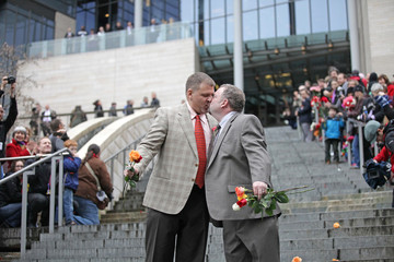 Brad and Jay McCanta kiss to a cheering crowd on the steps of City Hall after getting married at Seattle City Hall