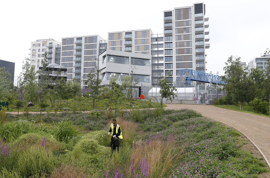 A landscape gardener works outside the Olympic Village at the Olympic Park in Stratford, the location of the London 2012 Olympic Games, in east London