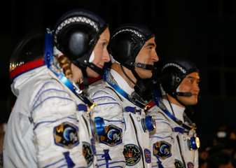 The ISS crew members Kate Rubins of the U.S., Anatoly Ivanishin of Russia and Takuya Onishi of Japan walk after donning space suits at the Baikonur cosmodrome, Kazakhstan