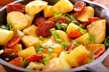 Baked potatoes with sausage chorizo and fried egg on frying pan