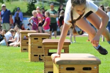 Flanken-Sprung über den Kasten beim Schulturnen auf dem Sportplatz
