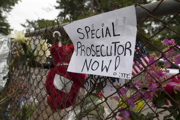 Protest signs and flowers adorn a fence during civil rights leader Rev. Al Sharpton's vigil at the site of the death of Walter Scott in North Charleston