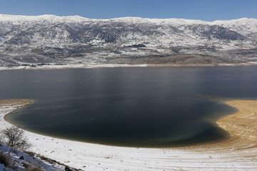 A snowy landscape is photographed around an artificial lake in Qaraoun, West Bekaa