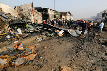 People gather at the site of a car bomb attack at a vegetable market in eastern Baghdad