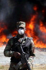 An army personnel stands guard while confiscated drugs burn inside a military base in Santo Domingo