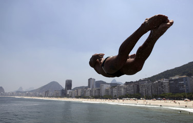 A man jumps into the waters of Leme beach in Rio de Janeiro