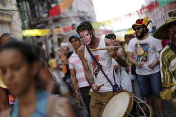 A reveller plays a musical instrument using a mask with picture of David Bowie during one of the many pre-carnival parties to take place in the neighbourhoods of Recife