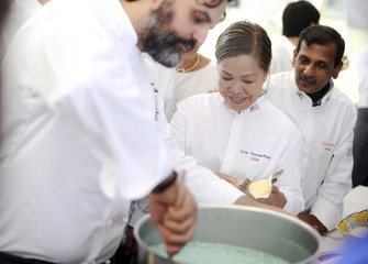"Chef Marco Stabile shows how to cook an Italian risotto to chefs Cristeta Comerford and Machindra Kasture during the annual meeting of the ""Club des Chefs des Chefs"" (CCC) in Livorno Ferraris"