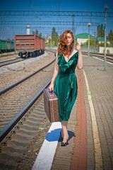 Gorgeous redhead woman in green velvet dress in vintage style with a suitcase on the platform