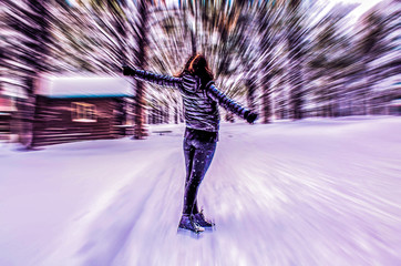 Young woman dancing / posing in snow on a cold winter day (motion blurred image)