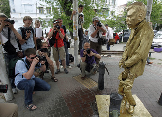 """Photographers take pictures of a statue of Soviet dictator Josef Stalin, styled after Brussels' """"Manneken Pis"""" in Kiev"""