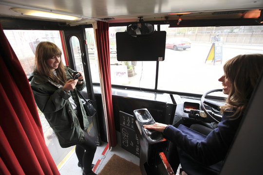 Diners take pictures of each other in the drivers seat on the Big Red Pizza Bus in Deptford, south east London