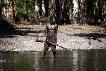 Australian Aboriginal hunter Roy Gaykamangu stands in a billabong after shooting a crocodile near the 'out station' of Yathalamarra, located on the outksirts of the community of Ramingining in East Arnhem Land
