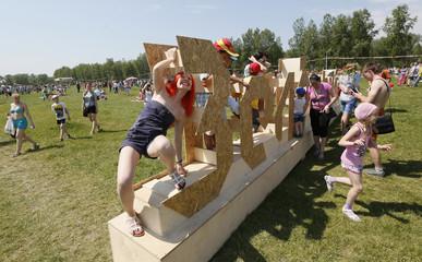 People climb on the festival's logo during the 5th Green Festival in Krasnoyarsk