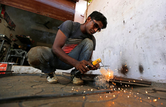 A worker welds a steel rod inside a door and window manufacturing unit on the outskirts of Ahmedabad