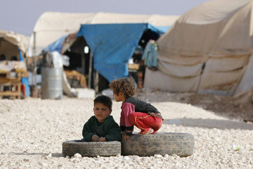 Children rest on tyres at the Bab Al-Salam refugee camp in Azaz, near the Syrian-Turkish border