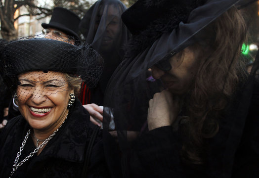 """Carnival revellers dressed up as mourners laugh as they pretend to cry during the """"The Burial of the Sardine"""" funeral procession in Madrid"""