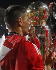 Benfica's Oscar Cardozo kisses the Portuguese Premier League trophy title after beating Olhanense at Luz stadium in Lisbon